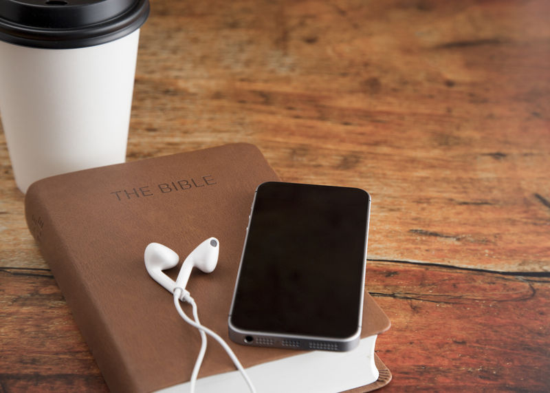 Bild vergrößern: Physical Bible and a Smart Phone with Earphones on a Wood Table